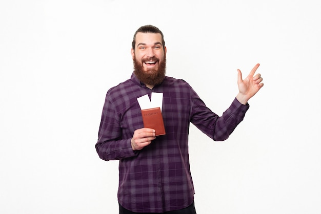 Happy young man with beard in checkered shirt holding tickets and pointing away
