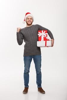 Счастливый молодой человек с бородой, держа подарок и руку вверх изолирован на белом