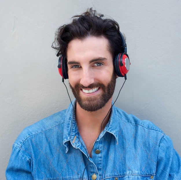 Happy young man with beard listening to music with headphones