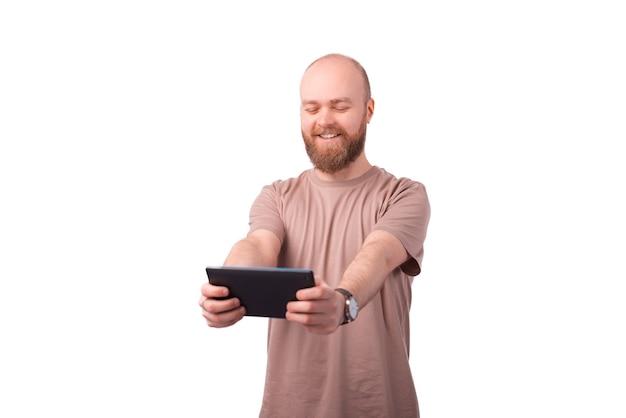 태블릿에서 온라인 게임을하는 수염을 가진 행복 한 젊은 사람