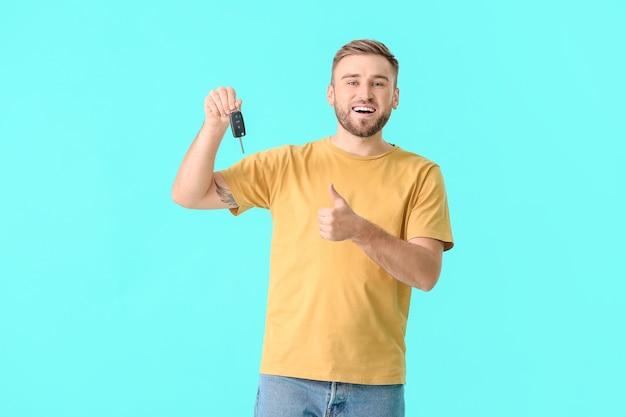 色の背景に車のキーを持つ幸せな若い男