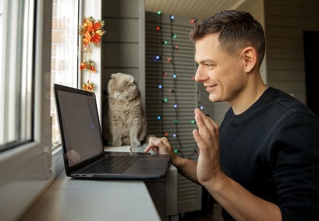 Счастливый молодой человек с кошкой дома с помощью зума, чтобы поздравить с рождеством его родственников