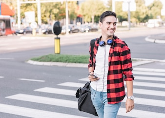 Happy young man with cellphone crossing street