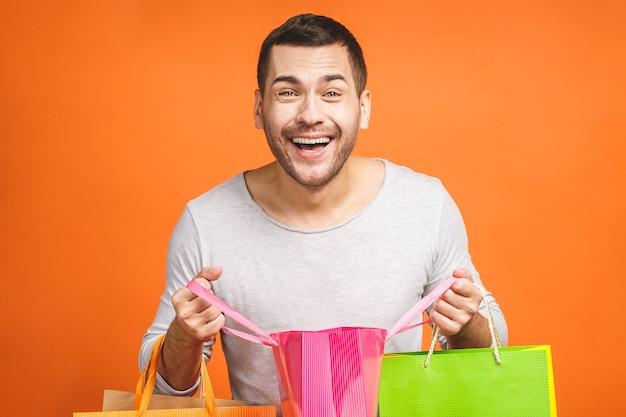 Счастливый молодой человек с красочными бумажными пакетами