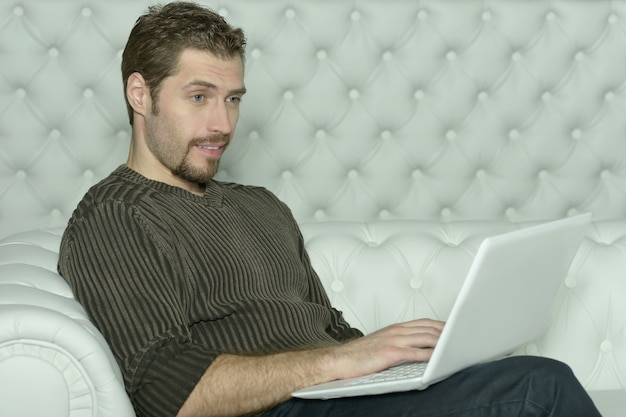 Happy  young man with computer laptop at home