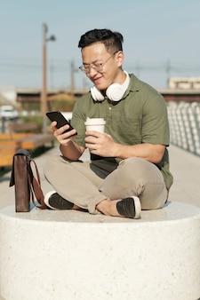 야외에서 음료수와 스마트폰 문자 메시지를 가진 행복한 청년