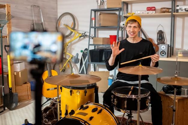 나지만 스마트 폰 카메라 앞에서 drumset에 앉아 행복 한 젊은 사람