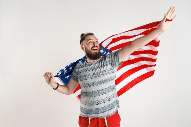 Счастливый молодой человек с флагом соединенных штатов америки, изолированные на белой студии.