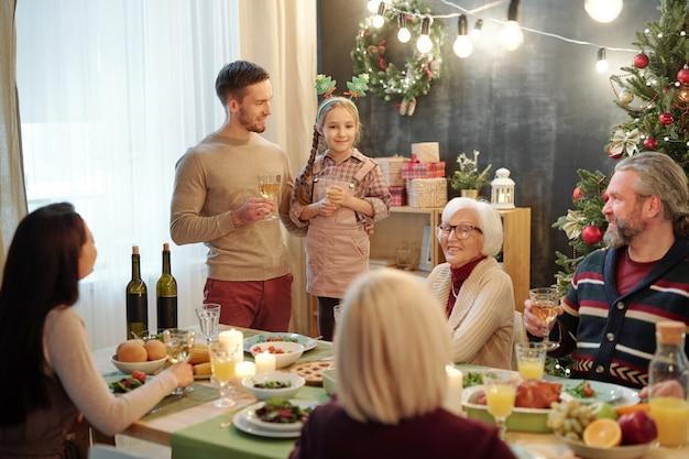 Счастливый молодой человек с бокалом вина и его милая маленькая дочь, стоящая перед остальной семьей на рождественском ужине