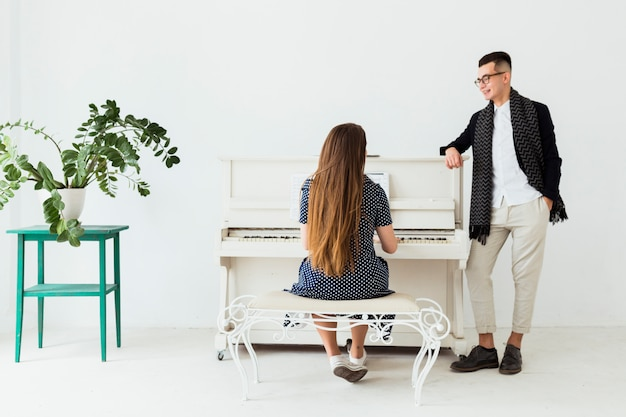 Happy young man with hand in her pocket looking at woman playing piano