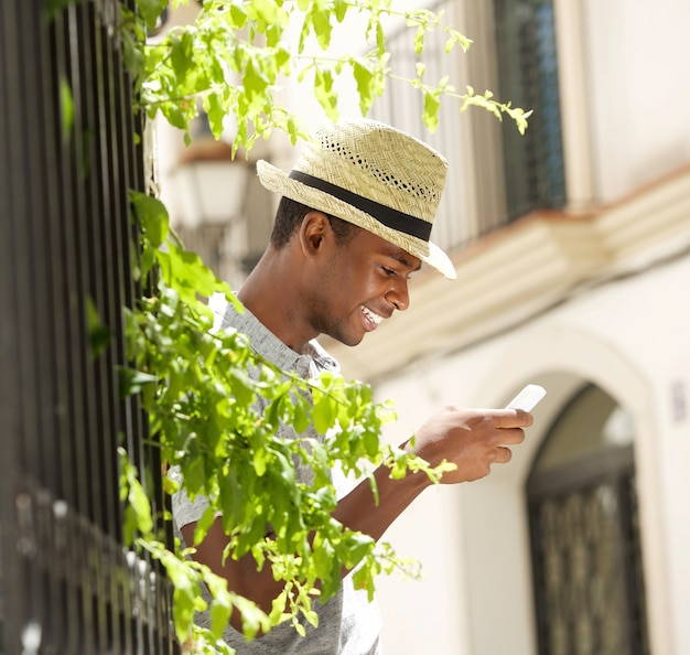 Happy young man with hat using mobile phone outside
