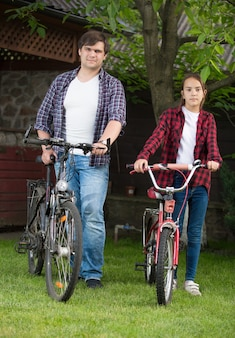 Happy young man with his daughter riding bicycles at park