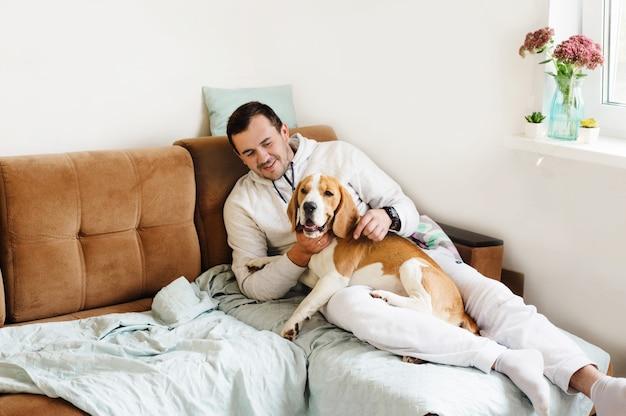 ソファに座っている彼の犬、ビーグルと幸せな若い男。