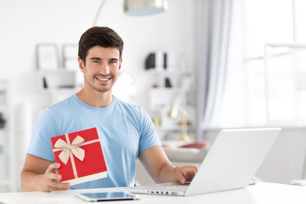 Happy young man with laptop holding gift while smiling