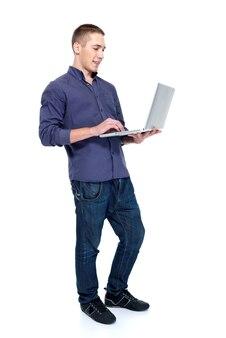 Giovane felice con il potrait di profilo del computer portatile - isolato su bianco