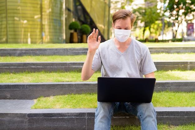 Счастливый молодой человек с маской видеовызова с помощью ноутбука, сидя на открытом воздухе