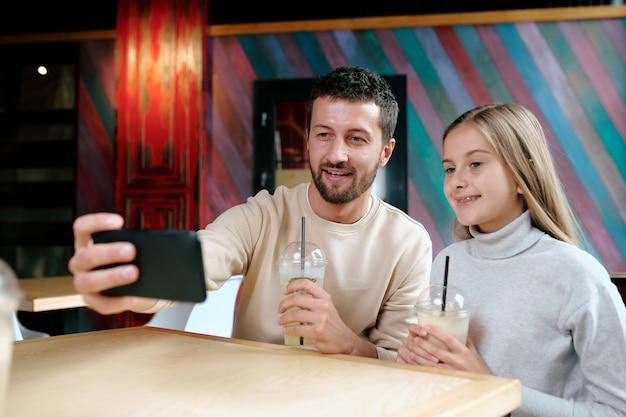 カフェに座ってカクテルを飲んでいる間彼の娘と一緒にselfieを取って携帯電話で幸せな若い男