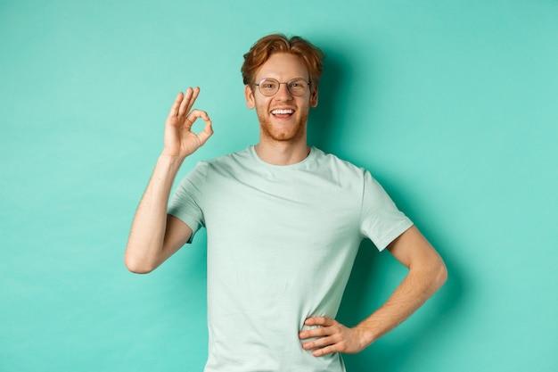 빨간 머리와 수염을 가진 행복한 청년, 안경과 티셔츠를 입고 만족스러운 미소를 지으며 확인 표시를 하고, 예라고 말하고, 승인하고, 동의하며, 청록색 배경 위에 서 있습니다.