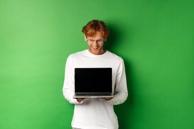 빨간 머리를 가진 행복 한 젊은 남자, 빈 노트북 화면을 표시 하 고 기쁘게 찾고 컴퓨터, 녹색 배경 쳐다 보면서 웃 고.