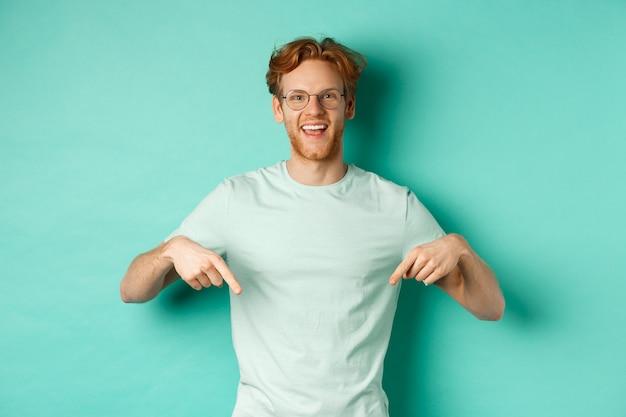 赤い髪、眼鏡とtシャツを着て、広告を表示し、笑顔で指を下に向け、ターコイズブルーの背景の上に立って幸せな若い男