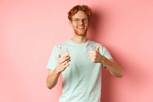 Happy young man with red messy hair, showing thumbs-up while using mobile phone, smiling and praising application, standing over pink background.