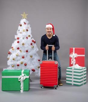 灰色の赤いスーツケースと幸せな若い男