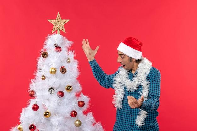 Felice giovane uomo con cappello di babbo natale in una camicia blu spogliata e guardando l'albero di natale sorprendentemente rosso