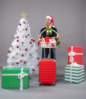 Happy young man with santa hat holding gift basket with both hands near white xmas tree on grey