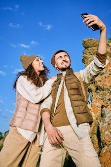 Счастливый молодой человек со смартфоном делает селфи с женой, стоящей рядом на фоне голубого неба и каменной скалы