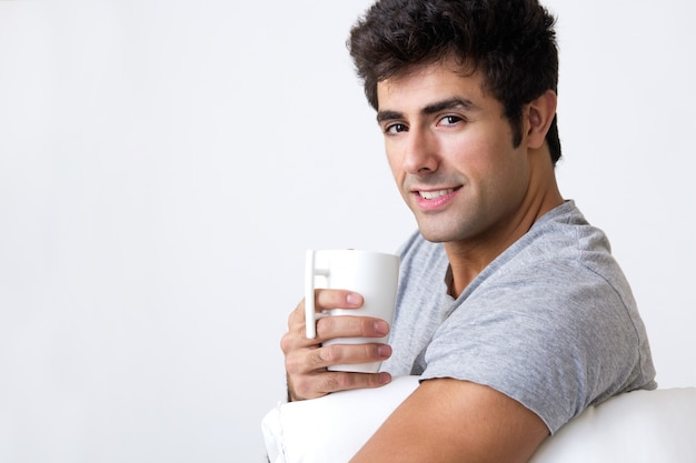 Happy young man with a steamy cup of coffee at home