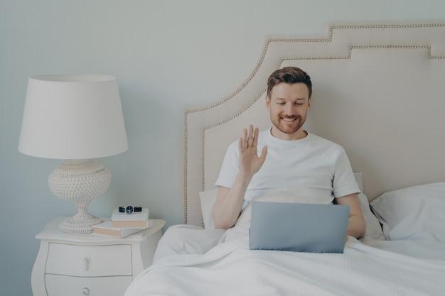 Счастливый молодой человек со щетиной машет рукой к ноутбуку во время онлайн-видеозвонка и сидит в постели, разговаривая со своими близкими друзьями в свободное время в выходные дома