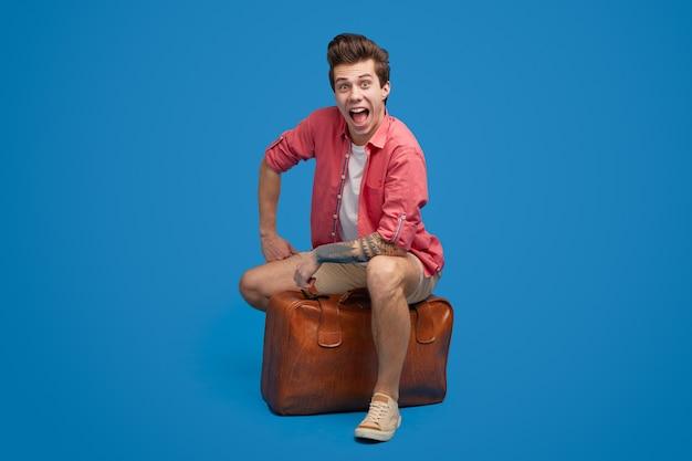 旅行の準備ができてスーツケースを持つ幸せな若い男