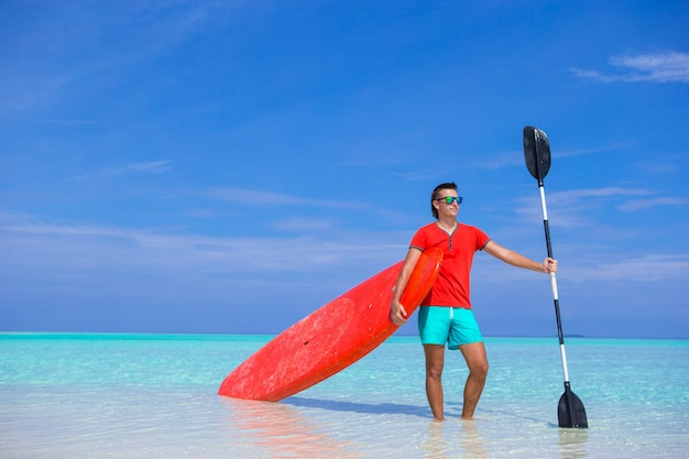 Happy young man with surfboard and paddle on the tropical coast