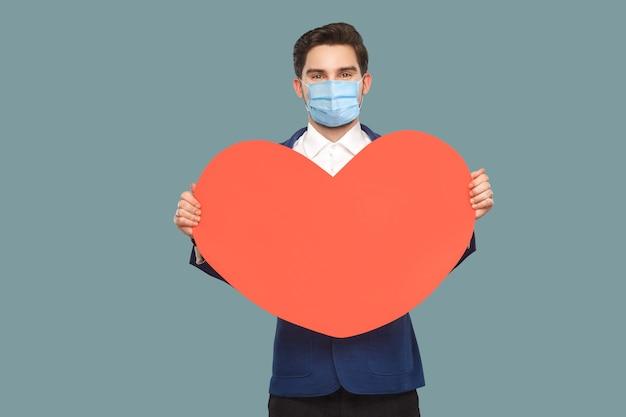 외과용 의료 마스크를 쓴 행복한 청년이 빨간색 큰 심장 모양을 들고 서 있습니다. 좋은 느낌으로 카메라를 찾고. 의학 및 건강 관리 개념입니다. 파란색 배경에 고립 된 실내, 스튜디오 촬영