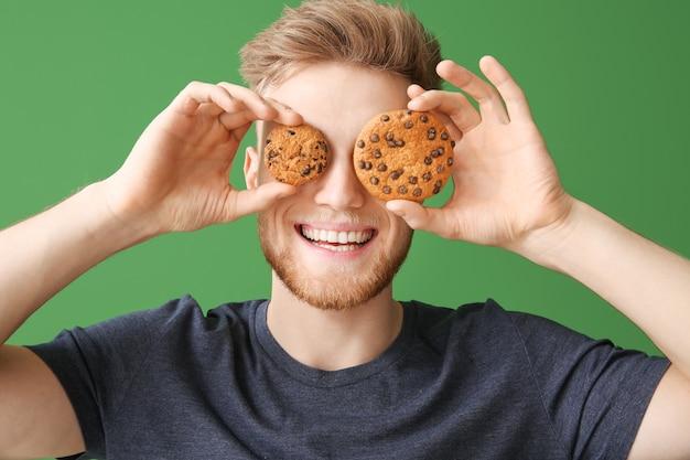 색상 표면에 맛있는 쿠키와 함께 행복 한 젊은 사람