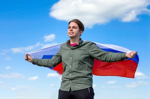 Счастливый молодой человек с флагом россии против голубого неба.