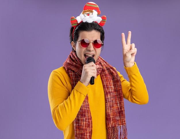 黄色のタートルネックの首の周りに暖かいスカーフと紫色の壁の上に立っているvサインを示すマイクの歌を保持している頭に面白い縁のメガネと幸せな若い男