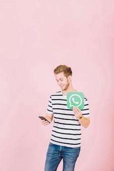 Счастливый молодой человек с whatsapp значок с помощью смартфона
