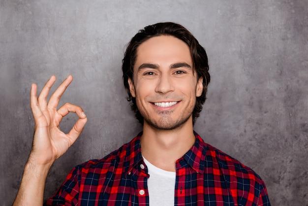 Счастливый молодой человек с белой улыбкой показывает знак ок