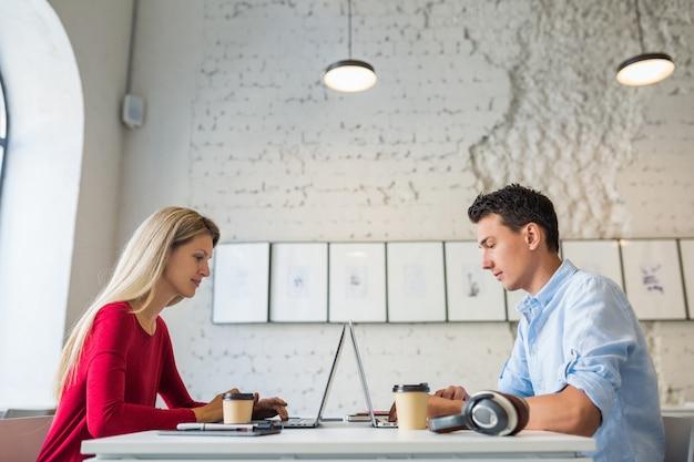 Felice giovane uomo e donna seduta al tavolo faccia a faccia, lavorando al computer portatile in ufficio di co-working