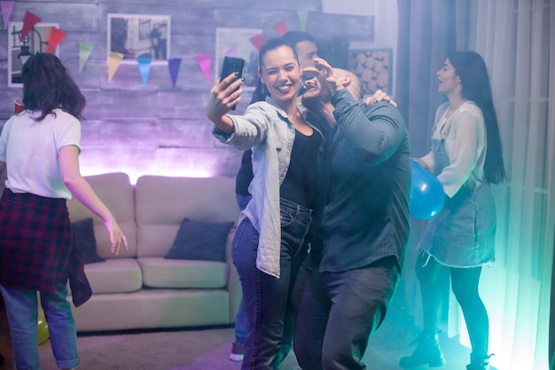 Happy young man and woman taking a selfie at a party with their friends. group of people dancing.
