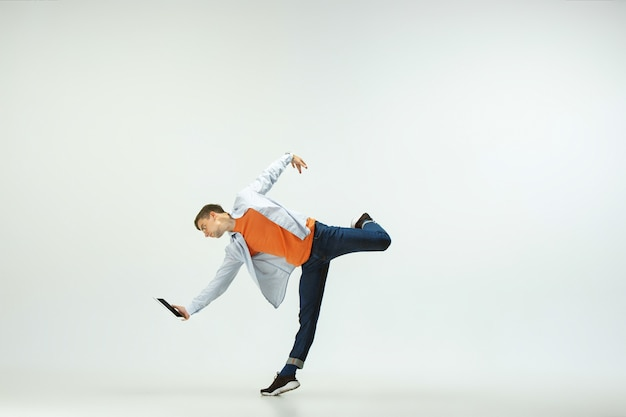 사무실에서 일하고, 점프와 캐주얼 옷이나 정장 흰색 배경에 고립 된 춤 행복 한 젊은 남자.