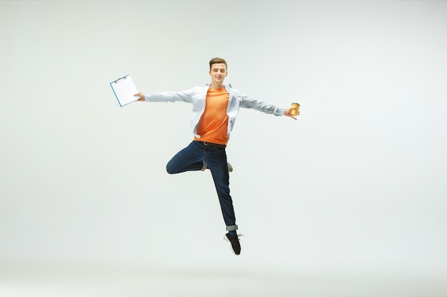 オフィスで働いて、白い背景で隔離のカジュアルな服やスーツでジャンプして踊る幸せな若い男。
