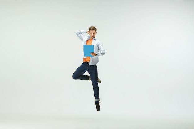 Happy young man working at office, jumping and dancing in casual clothes or suit isolated on white  background.