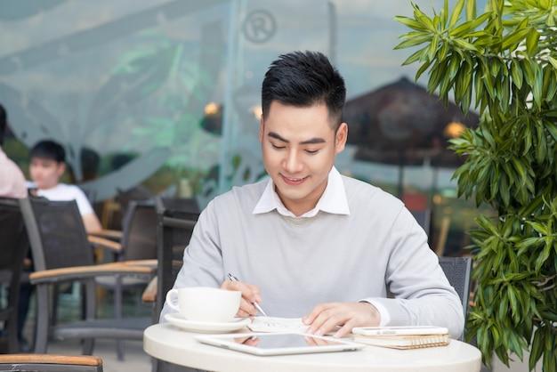 카페 바에서 커피 브레이크 동안 랩톱 컴퓨터에서 작업하는 행복 한 젊은 남자