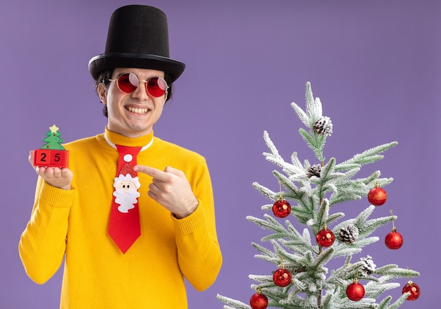 Happy young man in yellow turtleneck and glasses wearing black hat and funny tie holding cubes with number twenty five pointing
