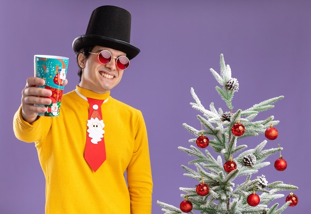 Felice giovane uomo in dolcevita giallo e occhiali indossando cappello nero e cravatta divertente che mostra la tazza di carta colorata sorridente allegramente in piedi accanto a un albero di natale su sfondo viola