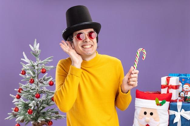 Felice giovane uomo in dolcevita giallo e occhiali indossando cappello nero tenendo il bastoncino di zucchero sorridente allegramente in piedi accanto a un albero di natale e presenta su sfondo viola