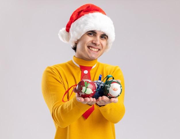 Felice giovane uomo in dolcevita giallo e cappello da babbo natale che tiene le palle di natale guardando la telecamera sorridendo allegramente in piedi su sfondo bianco