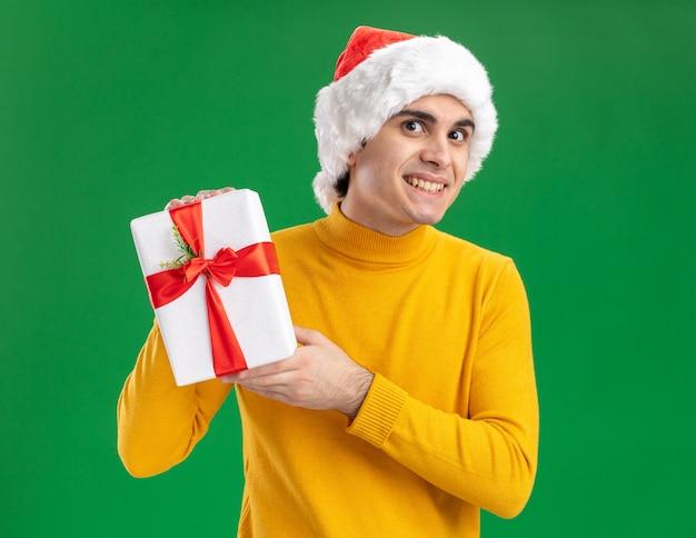 Felice giovane uomo in dolcevita giallo e cappello santa tenendo un presente guardando la telecamera sorridendo allegramente in piedi su sfondo verde